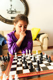 Girl playing chess. Cute happy girl playing chess Royalty Free Stock Image
