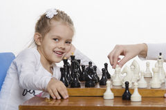 Girl playing chess in a good mood Stock Images