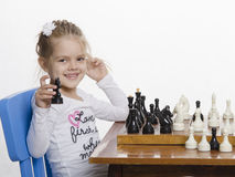 Girl playing chess in a good mood Stock Photos