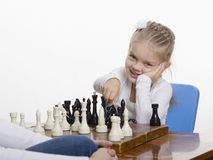 Girl playing chess in a good mood Stock Photo