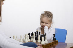 Girl playing chess, thinking about the next course of Stock Image