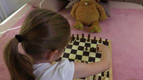Girl playing chess with toy stock footage