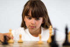 Girl playing chess Stock Images