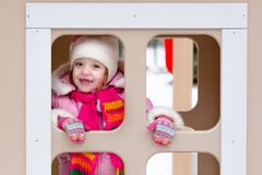 Girl playing on a children`s playground in winter stock image