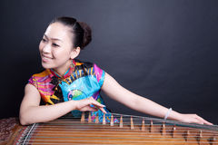 Girl playing Chinese zither. Girl sitting and playing Chinese zither Stock Image