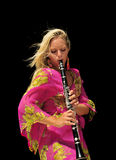 Girl Playing Clarinet Solo. Blonde girl in floral dress playing clarinet with feeling. Isolated on black background Stock Images