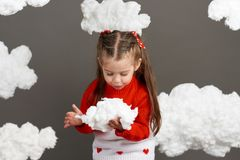 Girl playing with clouds, dressed in red sweater, shot in the studio on a gray background Stock Images