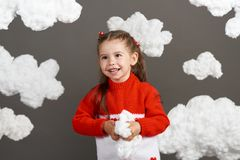Girl playing with clouds, dressed in red sweater, shot in the studio on a gray background Stock Photography