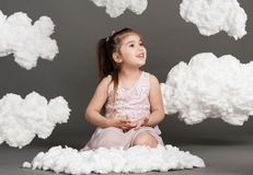 Girl playing with clouds, shot in the studio on a gray background Royalty Free Stock Photo