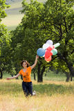 Girl playing with color balloons Stock Image