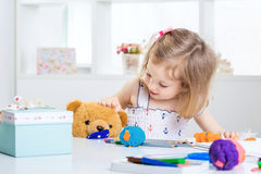 Girl playing with colored plasticine. Little girl playing with colored plasticine and drawing with crayons on the album. child child playing with Teddy bear Royalty Free Stock Image