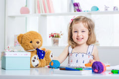 Girl playing with colored plasticine. Little girl playing with colored plasticine and drawing with crayons on the album. child child playing with Teddy bear Royalty Free Stock Photo