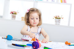 Girl playing with colored plasticine. Little girl playing with colored plasticine and drawing with crayons on the album. child having fun at home Royalty Free Stock Photography