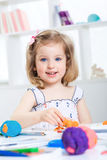 Girl playing with colored plasticine. Little girl playing with colored plasticine and drawing with crayons on the album. child having fun at home Royalty Free Stock Photo