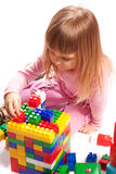 Girl  playing with colorful blocks. Little girl sitting at the floor and playing with colorful blocks Royalty Free Stock Image
