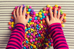 Girl playing with colorful sweets Stock Images