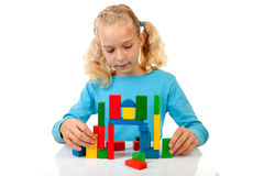 Girl is playing with colorful wooden blocks Royalty Free Stock Photo