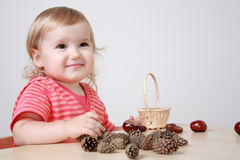 Girl playing with cones and chestnuts Stock Image