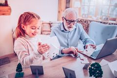 Girl playing constructor with her grandfather at home stock images