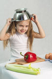 Girl playing in the cook put on a colander on his head Royalty Free Stock Images