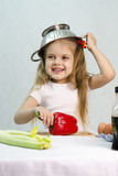 Girl playing in the cook put on a colander on his head Royalty Free Stock Photo