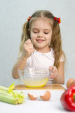 Girl playing in a cook churn whisk the eggs in a glass bowl Royalty Free Stock Photos