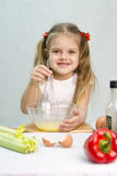 Girl playing in a cook churn whisk the eggs in a glass bowl Royalty Free Stock Photo