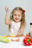 Girl playing in a cook churn whisk the eggs in a glass bowl Stock Photo
