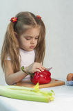 Girl playing in a cook cuts the knife red pepper Stock Photos