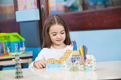 Girl Playing With Craft In Classroom Stock Photos
