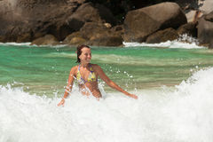 Girl playing with crashing waves in sunny day royalty free stock photography