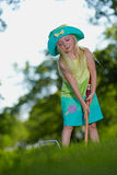Girl playing croquet. Cute blonde girl playing croquet outside in the grass Royalty Free Stock Image