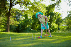 Girl playing croquet. Cute young girl playing croquet on grass with trees in background Stock Photo