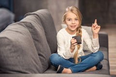 Girl playing with cube. Cute little girl playing with cube and pointing up with finger Stock Photo