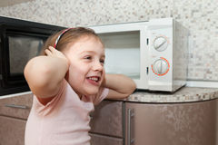 Girl playing with dangerous kitchen appliance royalty free stock image