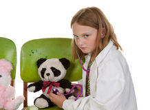Girl playing doctor with her toys Royalty Free Stock Photos