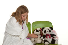 Girl playing doctor with her toys Stock Photo