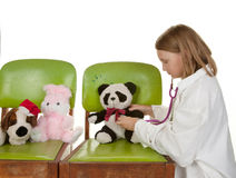 Girl playing doctor with her toys Stock Image
