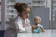 Girl playing doctor Stock Image