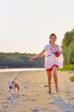 Girl playing with dog. On beach Stock Image
