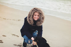 Girl playing with a dog. On the beach Royalty Free Stock Images