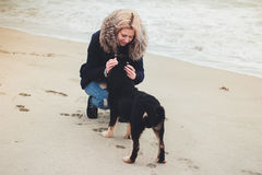Girl playing with a dog. On the beach Stock Photo