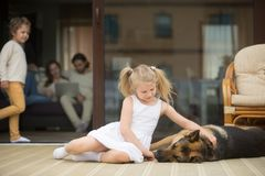 Girl playing with dog outside, family inside house at background Stock Photography
