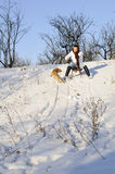 Girl playing with dog in snow Stock Image