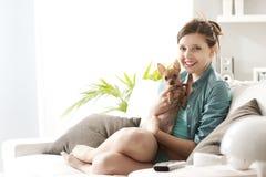 Girl playing with dog on sofa Stock Image