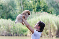 Girl playing with dog. Teenage girl with long braids standing there smiling with a spitz on the banks of the river royalty free stock photo