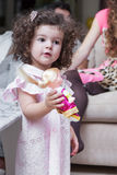 Girl playing with a doll. Baby girl plays with a doll, her parents find out the relationship in the background stock photo