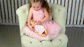 Girl playing doll holding and embracing. Cute little girl holding and embracing her doll stock footage