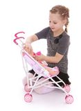 Girl playing with a doll put her in the stroller Royalty Free Stock Photo