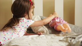 Girl Playing with Doll. She put her to sleep and gives her a pacifier. Happy childhood. Children`s games. Mother`s stock video footage